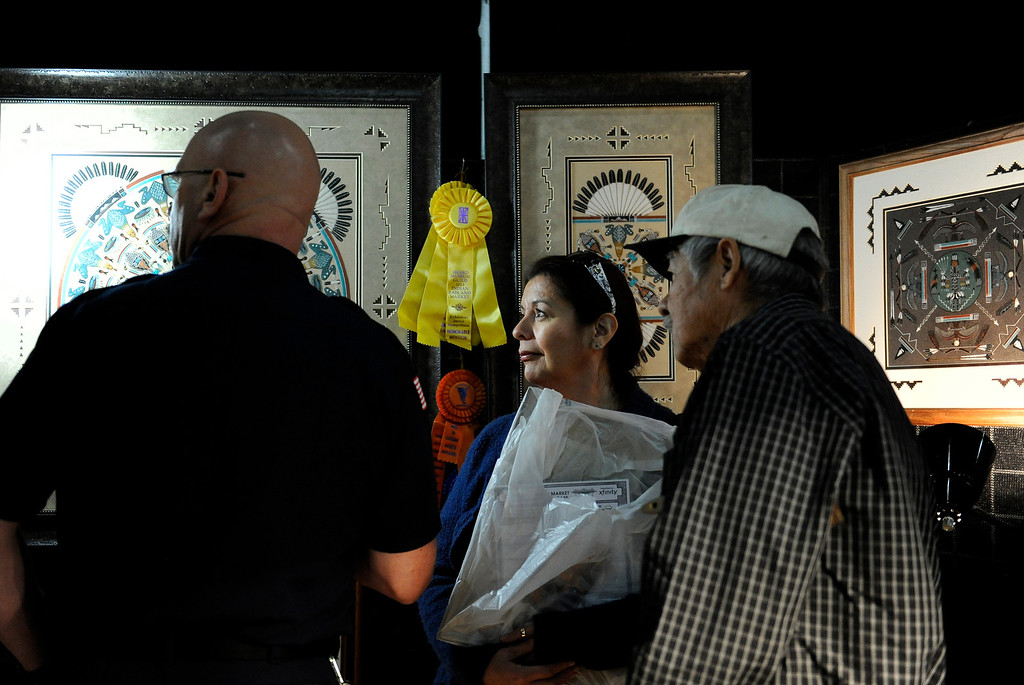 . JoAnn Patterson, center, looks at artwork with her husband, left, for their new home during the Colorado Indian Market on Jan. 19 at the Denver Mart in Denver, Colo. Photo by Jamie Cotten, Special to The Denver Post