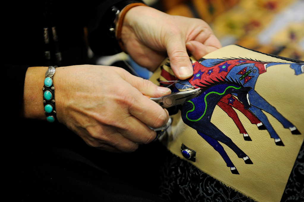 . Kathy Kershaw puts beads on one of her handmade, hand-dyed leather purses on Jan. 19 during the Colorado Indian Market at the Denver Mart in Denver, Colo. Photo by Jamie Cotten, Special to The Denver Post