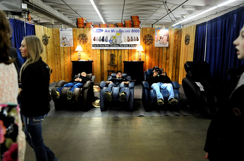 . Tate Knapp, left to right, James Miner and Andy Higgins enjoy massaging chairs as they watch people pass by on Jan. 19 during the National Western Stock Show at the Denver Coliseum. Knapp was there to show sheep, Miner there to show pigs, and Higgins there to show cattle. Photo by Jamie Cotten, Special to The Denver Post