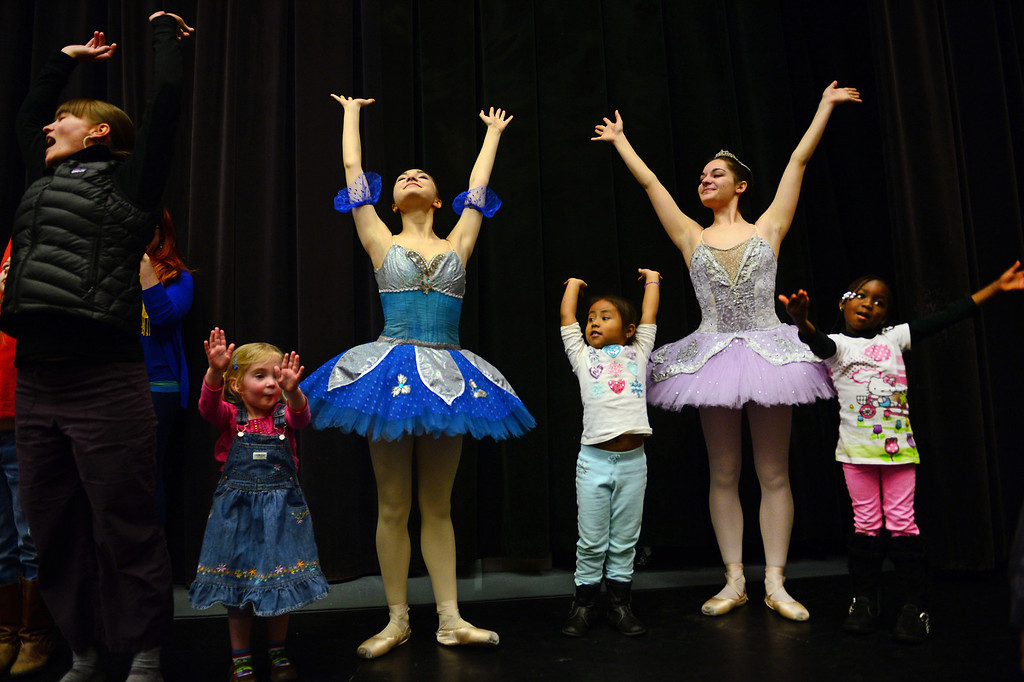 """. DENVER, CO - FEBRUARY 9,  2014:  Ballet dancers Ryan Lee, in blue, and Emma Daddario, in purple, lead from left to right:  Eve Goeke, 3, Marlene Reyes, 5 and Wonenouon Some, 5, in some warm up dance moves after their performances at the Children\'s Museum in Denver,  CO on February 9, 2014. Colorado Ballet hosts \""""From the Page to the Stage\"""" performances at schools, hospitals, museums and libraries.  During these performances, Colorado Ballet Studio Company dancers perform excerpts from ballets based on Shakespeare and the classics such as the upcoming production of Cinderella.  The outreach program makes more than 60,000 contacts each year.   (Photo By Helen H. Richardson/ The Denver Post)"""