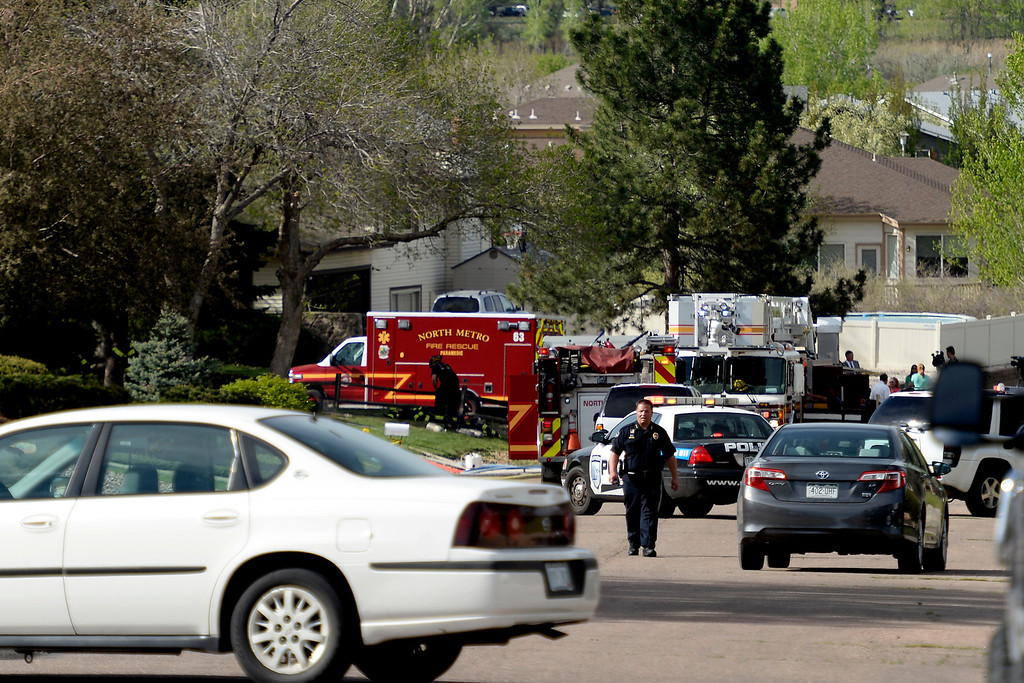 . An officer walks up the street as crews work on the crash site. A plane crashed into a home in Northglenn 110th Avenue and Livingston on May 5, 2014. (Photo by AAron Ontiveroz/The Denver Post)