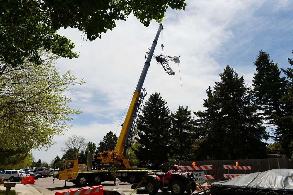 . NORTHGLENN, CO. - MAY 06: A crane lifts up the wreckage of an aircraft out of the back of a home Tuesday morning, May 06, 2014. The airplane crashed into the back of the home at 11006 Livingston Dr. in Northglenn the day before, May 05, 2014.  The pilot walked away from the crash uninjured, nobody was at the home at the time of the crash. (Photo By Andy Cross / The Denver Post)