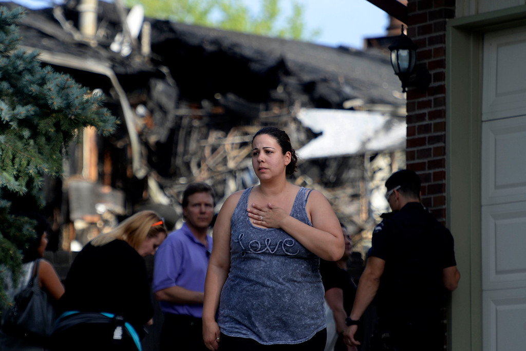 . A friend of the residents (who asked not to be named) walks away from the scene of the accident behind police tape. A plane crashed into a home in Northglenn 110th Avenue and Livingston on May 5, 2014. (Photo by AAron Ontiveroz/The Denver Post)