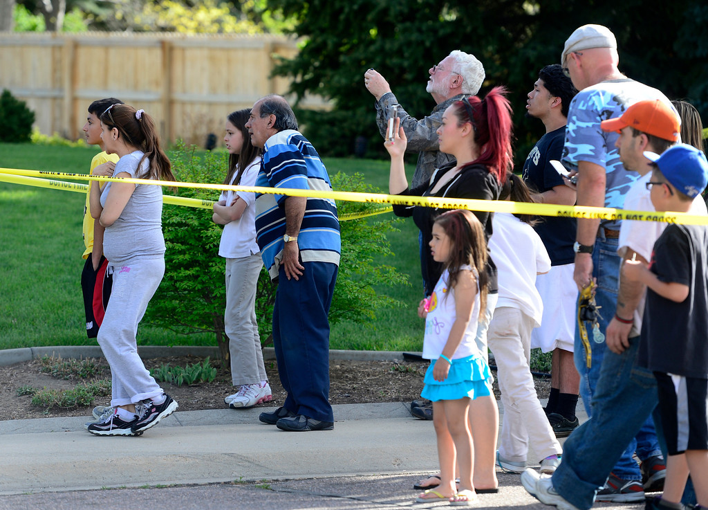 . A crowd gathers behind police to tape to try and get a look at the home where emergency crews responded in Northglenn after small plane crashed in to it on Monday, May 5, 2014. (Kathryn Scott Osler, The Denver Post)