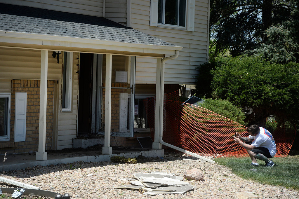 . NORTHGLENN, CO. - MAY 06: Homeowner, Matthew Richardson, takes pictures of his damaged home through the front door Tuesday May 06, 2014 a day after a small plane crashed into the back of his house at 11006 Livingston Dr. in Northglenn. The pilot walked away from the crash uninjured, Richardson and family were not home at the time of the crash.  (Photo By Andy Cross / The Denver Post)