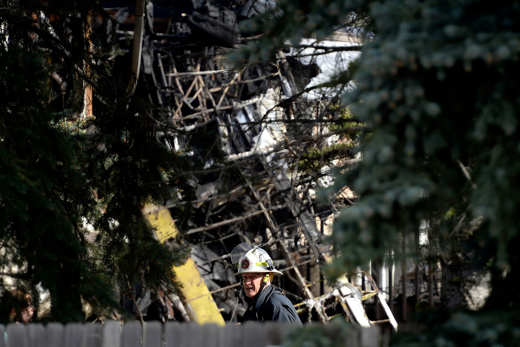 . A North Metro fireman stands near the scene of the crash. A plane crashed into a home in Northglenn 110th Avenue and Livingston on May 5, 2014. (Photo by AAron Ontiveroz/The Denver Post)