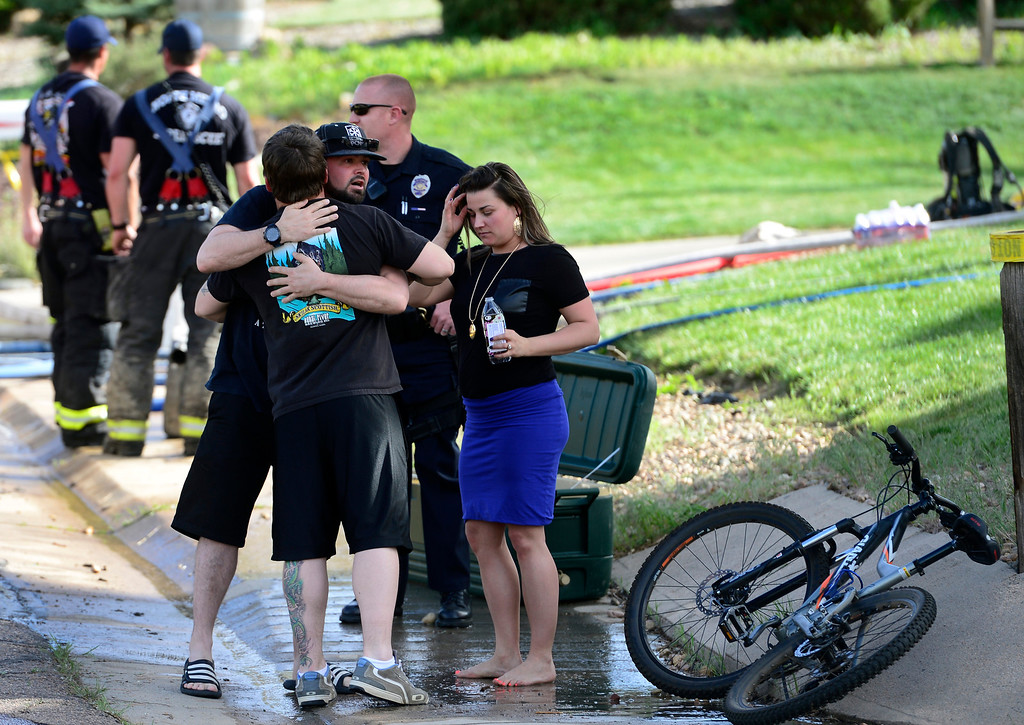 . Several people gather with police and firefighters in front of the home where emergency crews responded in Northglenn after small plane crashed in to it on Monday, May 5, 2014. (Kathryn Scott Osler, The Denver Post)