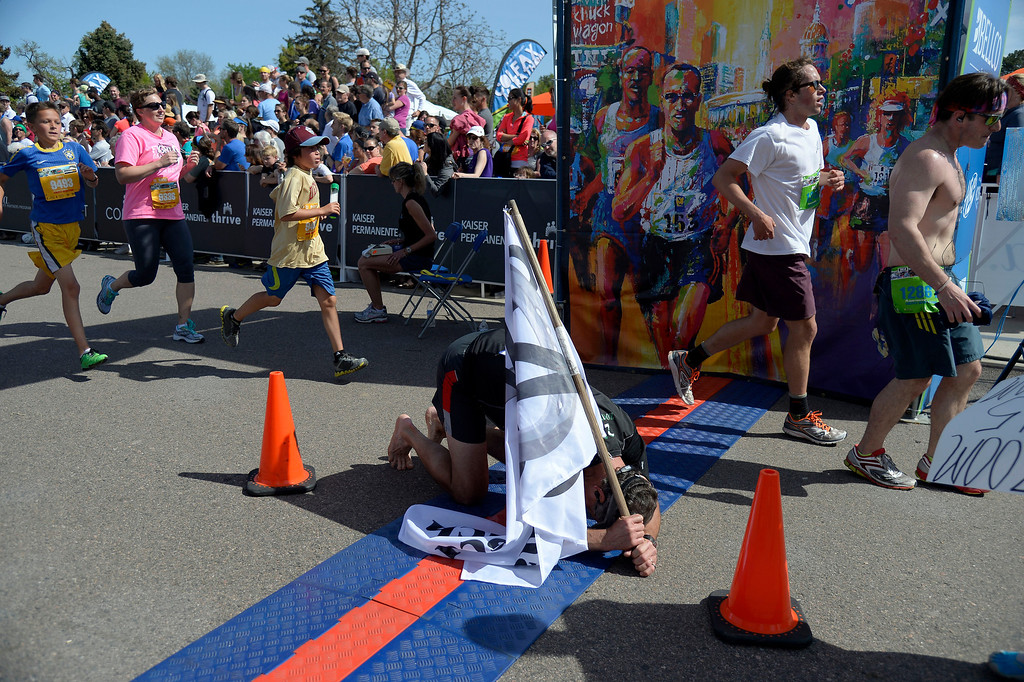 . Paul Messenich of Zuma\'s Rescue Ranch falls to the ground as he crossed the finish line with a time of 3:54:29 during the 9th annual Colfax Marathon May 18, 2014. The 26.2 mile Marathon runs through Denver�s iconic landmark Mile High Stadium (twice), Sloan�s Lake, City Park, Colfax Avenue through Lakewood and Aurora. The Marathon started and finished in City Park where runners enjoyed the rest of the day listening to music by Chris Daniels and the Kings. (Photo by John Leyba/The Denver Post)