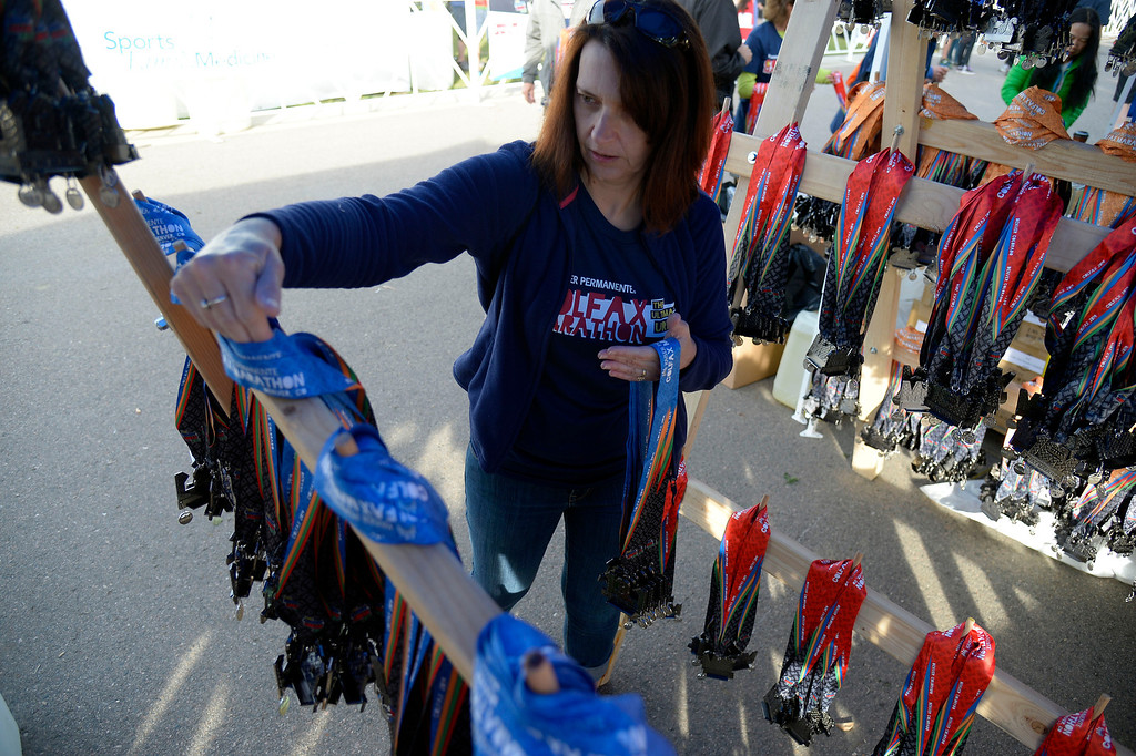 . Paula Price of Highlands Ranch hangs the medals that are handed out at the 9th annual Colfax Marathon May 18, 2014. The 26.2 mile Marathon runs through Denver�s iconic landmark Mile High Stadium (twice), Sloan�s Lake, City Park, Colfax Avenue through Lakewood and Aurora. The Marathon started and finished in City Park where runners enjoyed the rest of the day listening to music by Chris Daniels and the Kings. (Photo by John Leyba/The Denver Post)