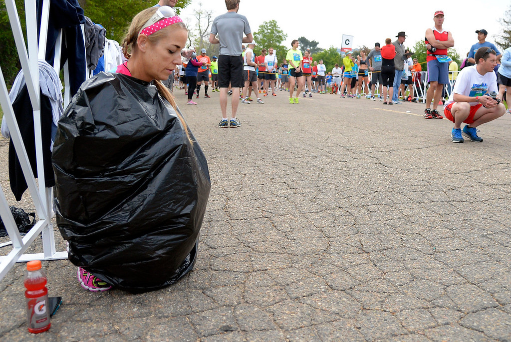 . Karen Flynn of San Diego keeps warm in a trash bag before the start of the 1/2 marathon at the 9th annual Colfax Marathon May 18, 2014. The 26.2 mile Marathon runs through Denver�s iconic landmark Mile High Stadium (twice), Sloan�s Lake, City Park, Colfax Avenue through Lakewood and Aurora. The Marathon started and finished in City Park where runners enjoyed the rest of the day listening to music by Chris Daniels and the Kings. (Photo by John Leyba/The Denver Post)