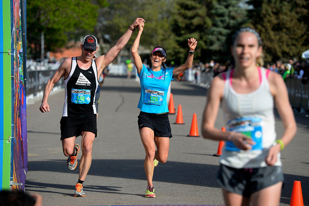 . Ryan Otto and his wife Temple Hayles raise their arms high as they cross the finish line of the 1/2 marathon in the 9th annual Colfax Marathon May 18, 2014. The 26.2 mile Marathon runs through Denver�s iconic landmark Mile High Stadium (twice), Sloan�s Lake, City Park, Colfax Avenue through Lakewood and Aurora. The Marathon started and finished in City Park where runners enjoyed the rest of the day listening to music by Chris Daniels and the Kings. (Photo by John Leyba/The Denver Post)