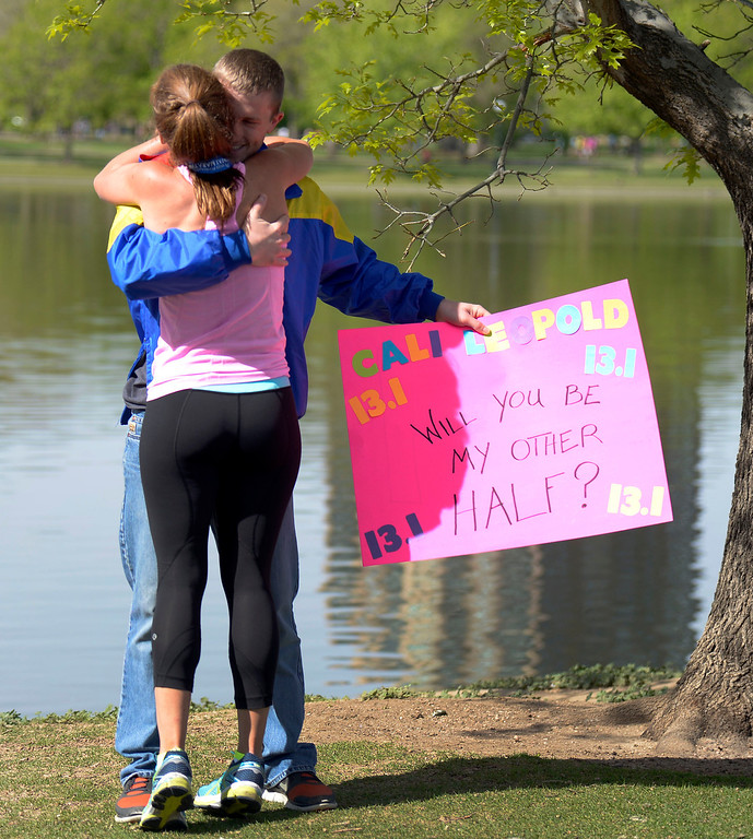 . Cali Leopold hugs Justin Horner after he proposed to her after she finished her 1/2 marathon run in the 9th annual Colfax Marathon May 18, 2014. The 26.2 mile Marathon runs through Denver�s iconic landmark Mile High Stadium (twice), Sloan�s Lake, City Park, Colfax Avenue through Lakewood and Aurora. The Marathon started and finished in City Park where runners enjoyed the rest of the day listening to music by Chris Daniels and the Kings. (Photo by John Leyba/The Denver Post)