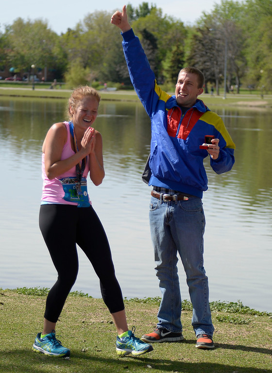 . Justin Horner  gives the thumbs up as Cali Leopold says yes after he proposed to her after she finished her 1/2 marathon run in the 9th annual Colfax Marathon May 18, 2014. The 26.2 mile Marathon runs through Denver�s iconic landmark Mile High Stadium (twice), Sloan�s Lake, City Park, Colfax Avenue through Lakewood and Aurora. The Marathon started and finished in City Park where runners enjoyed the rest of the day listening to music by Chris Daniels and the Kings. (Photo by John Leyba/The Denver Post)