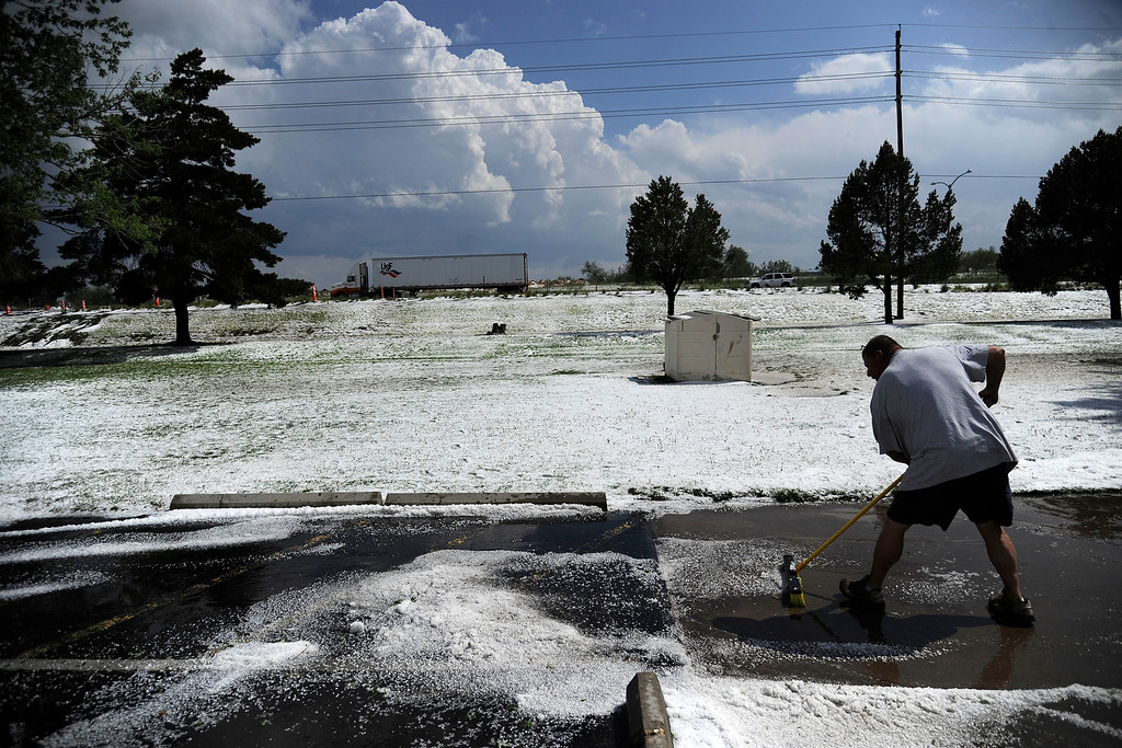 . AURORA, CO - MAY 21: Rob Post sweeps hail and clears water after hail pounded Woodshire Mobile Park. A hail storm hit the Denver metro area on Wednesday, May 21, 2014. (Photo by AAron Ontiveroz/The Denver Post)