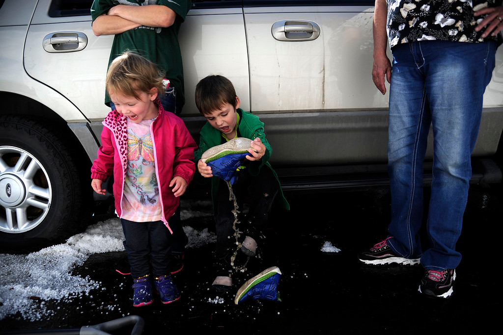 . AURORA, CO - MAY 21: Cole, 4, Cogar dumps water from his sneaker as his sister, Alyssa, 2, laughs after hail pounded Woodshire Mobile Park. A hail storm hit the Denver metro area on Wednesday, May 21, 2014. (Photo by AAron Ontiveroz/The Denver Post)