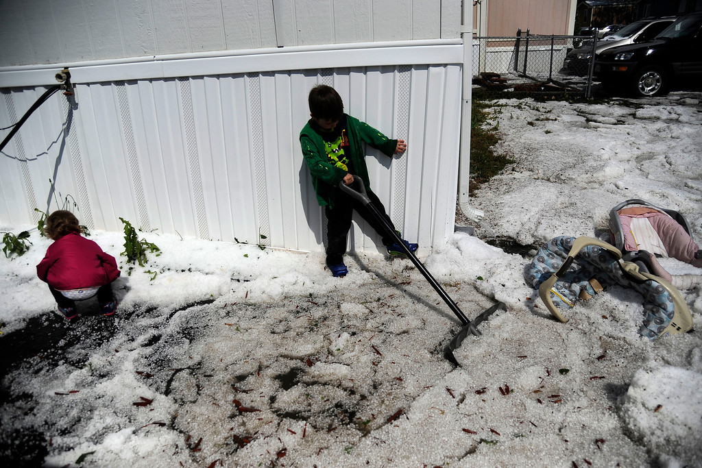 . AURORA, CO - MAY 21: Cole, 4, and Alyssa, 2, Cogar clean up after hail pounded Woodshire Mobile Park. A hail storm hit the Denver metro area on Wednesday, May 21, 2014. (Photo by AAron Ontiveroz/The Denver Post)