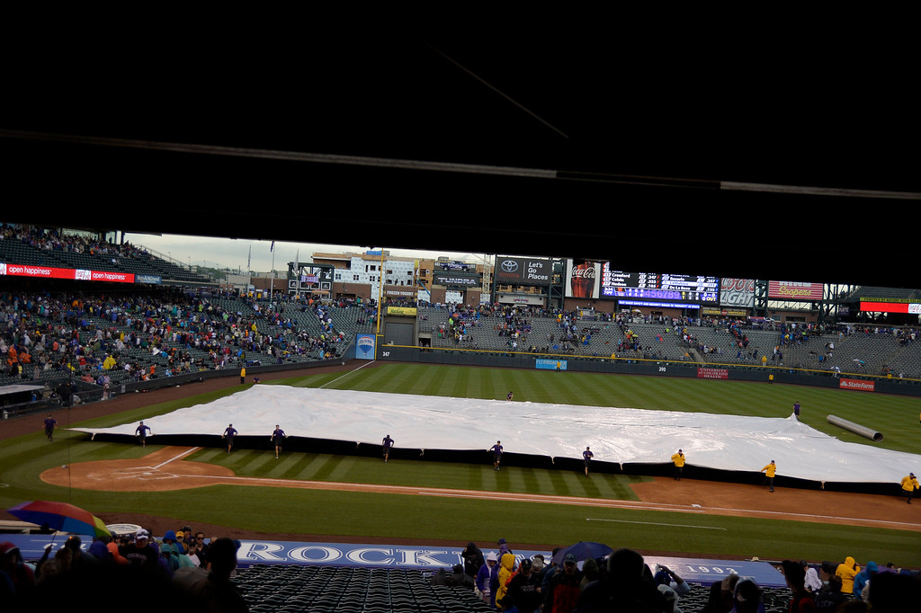 . DENVER, CO - MAY 22: Grounds crew roll out the tarp to cover the field as play was suspended for rain and lightning int he area during the Colorado Rockies San Francisco game May 22, 2014 at Coors Field. (Photo by John Leyba/The Denver Post)