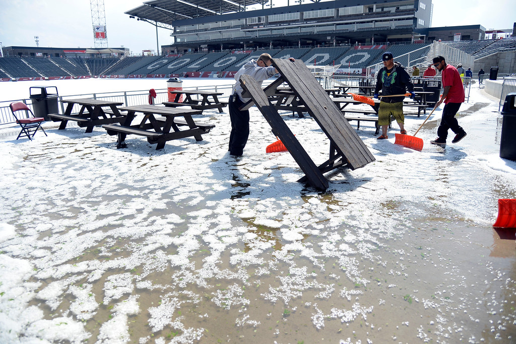 . COMMERCE CITY, CO - MAY 21: Grounds crew try to drain the water and hail from the picnic area at Dick\'s Sporting Goods Park. Hail pounded Commerce City blanketing the field at Dick\'s Sporting Goods Park May 21, 2014 where they will hold the class 4A and 5A state soccers finals. (Photo by John Leyba/The Denver Post)