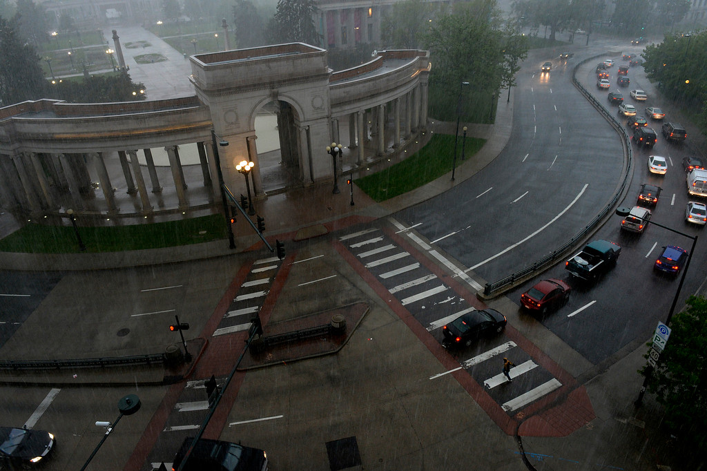. A pedestrian crosses Colfax Ave during afternoon rain in Denver, CO May 22, 2014. Heavy rain and hail pelted the Front Range on Thursday, the third consecutive day of severe storms. (Photo By Craig F. Walker / The Denver Post)