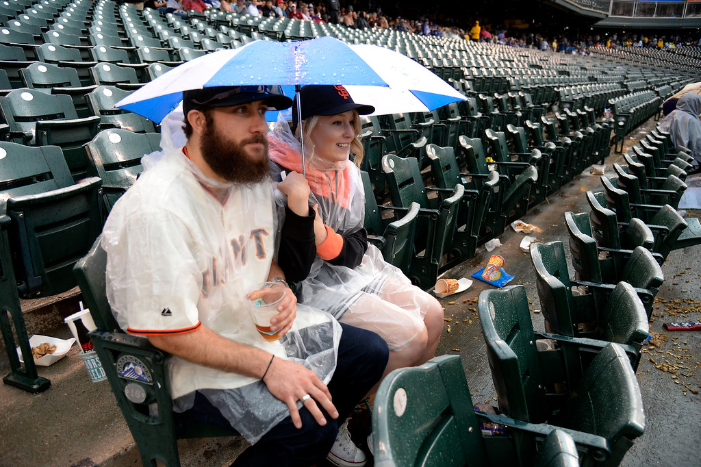 . DENVER, CO - MAY 22: Alex and Angela Martinson huddle under an umbrella during a rain delay at the Colorado Rockies San Francisco game May 22, 2014 at Coors Field. (Photo by John Leyba/The Denver Post)