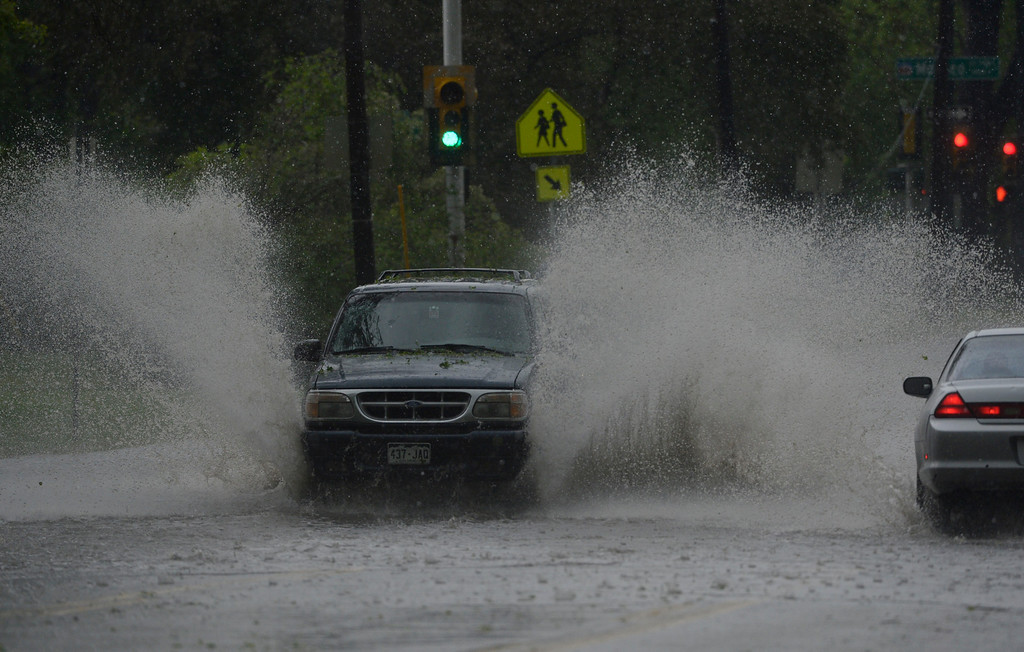 . An SUV navigates street flooding on Montview Blvd near Monaco during a heavy rain/hail storm  Wednesday afternoon, May 21, 2014. (Photo By Andy Cross / The Denver Post)