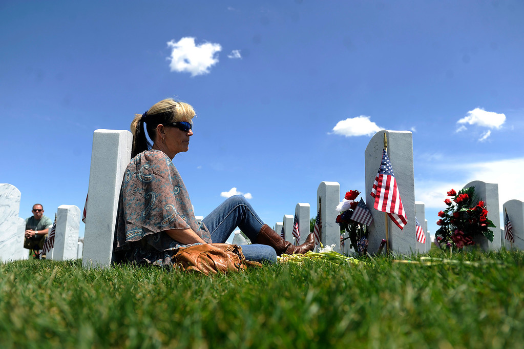 . Karen Suss listens to the song Cemetery Gates by Pantera on her phone as she visits her Jason R Slack\'s gravesite at Fort Logan Cemetery in Denver, Colorado on May 26, 2014. Cemetery Gates was Slack\'s favorite song. (Photo by Seth McConnell/The Denver Post)