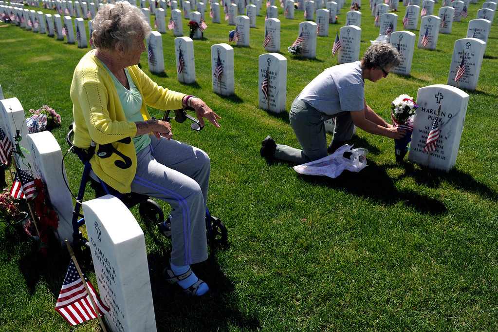 . Sue Puck, left, watches her daughter-in-law, Benita Puck, place flowers on Sue\'s husband, Harlen D Puck\'s, grave during a Memorial Day ceremony at Fort Logan Cemetery in Denver, Colorado on May 26, 2014. (Photo by Seth McConnell/The Denver Post)