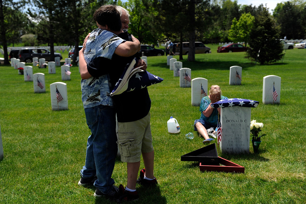 . Christian Stevens, 16, gets a hug from his grandpa Donald C Hesse II as Sue Hesse weeps in the background after Donald taught Christian how to properly fold the American flag in front of the grave of Donald\'s father, Donald C Hesse, during a Memorial Day ceremony at Fort Logan Cemetery in Denver, Colorado on May 26, 2014. (Photo by Seth McConnell/The Denver Post)