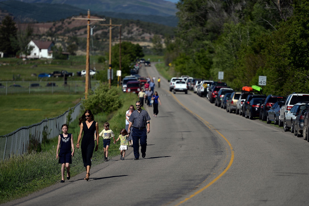 . Attendees arrive in droves, many of whom parked nearly a mile away, before the memorial service for the three men who went missing in the Mesa County mudslide. Hundreds of community members gathered for the memorial service at Plateau Valley High School on Sunday, June 01, 2014. (Photo by AAron Ontiveroz/The Denver Post)