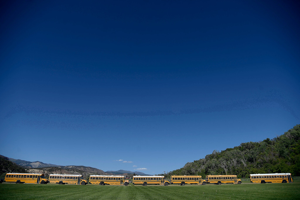 . School buses line the football field before the memorial service for the three men who went missing in the Mesa County mudslide. Hundreds of community members gathered for the memorial service at Plateau Valley High School on Sunday, June 01, 2014. (Photo by AAron Ontiveroz/The Denver Post)