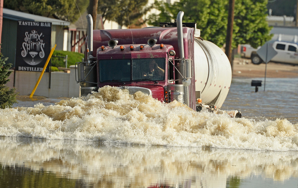 . A truck drives through the flood water in Greeley, June 3, 2014. A flood warning for the Poudre River near Greeley has been extended through Sunday. (Photo by RJ Sangosti/The Denver Post)