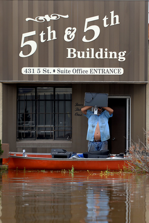 . Robert Villa saves computer equipment from DBE Manufacturing after an area of town flooded. A heavy rain caused parts of Greeley to flood on Monday, June 2, 2014. (Photo by AAron Ontiveroz/The Denver Post)