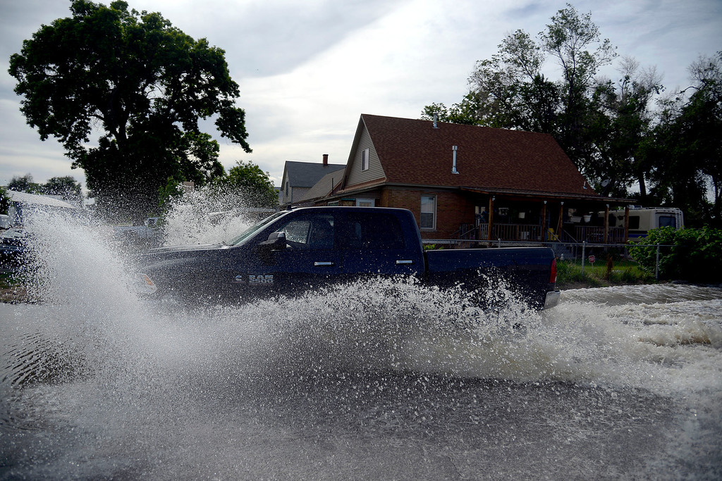 . A man in a big truck makes waves in the flood waters after an area of town flooded near Fourth Avenue. A heavy rain caused parts of Greeley to flood on Monday, June 2, 2014. (Photo by AAron Ontiveroz/The Denver Post)