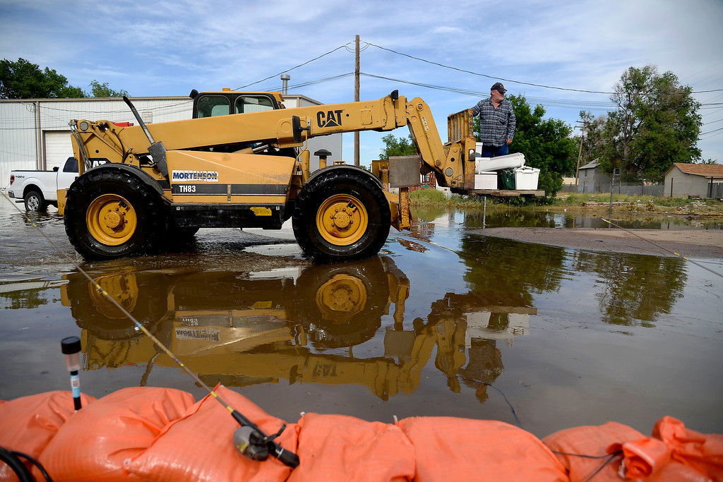 . A man rides atop heavy equipment to stay dry after an area of town flooded. A heavy rain caused parts of Greeley to flood on Monday, June 2, 2014. (Photo by AAron Ontiveroz/The Denver Post)