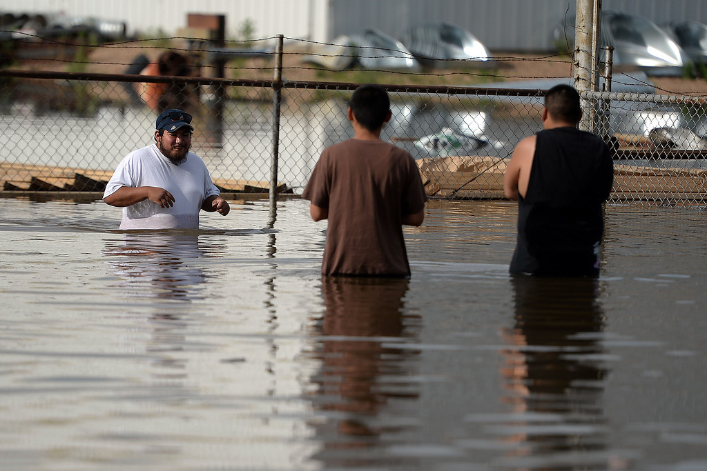 . Dimas Macias wades through the deep as Isaiah Macias and Dominique Jones look on after an area of town flooded. A heavy rain caused parts of Greeley to flood on Monday, June 2, 2014. (Photo by AAron Ontiveroz/The Denver Post)