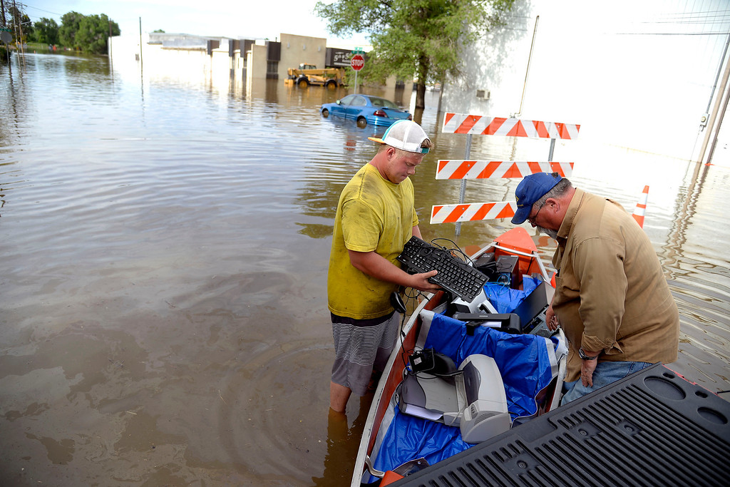 . Keegan Meyer (left) and Jim Trimble save computer equipment from DBE Manufacturing after an area of town flooded. A heavy rain caused parts of Greeley to flood on Monday, June 2, 2014. (Photo by AAron Ontiveroz/The Denver Post)