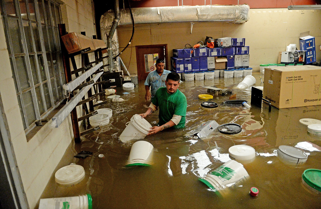 . Jay Torres, front, and Robert Frank Villa, both of DBE Manufacturing and Supply in Greeley, look for items to save from the shop where they work as water continues to rise along the Poudre River, June 3, 2014. A flood warning for the Poudre River near Greeley has been extended through Sunday. (Photo by RJ Sangosti/The Denver Post)