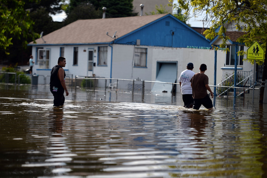 . A group of men test the waters after an area of town flooded. A heavy rain caused parts of Greeley to flood on Monday, June 2, 2014. (Photo by AAron Ontiveroz/The Denver Post)