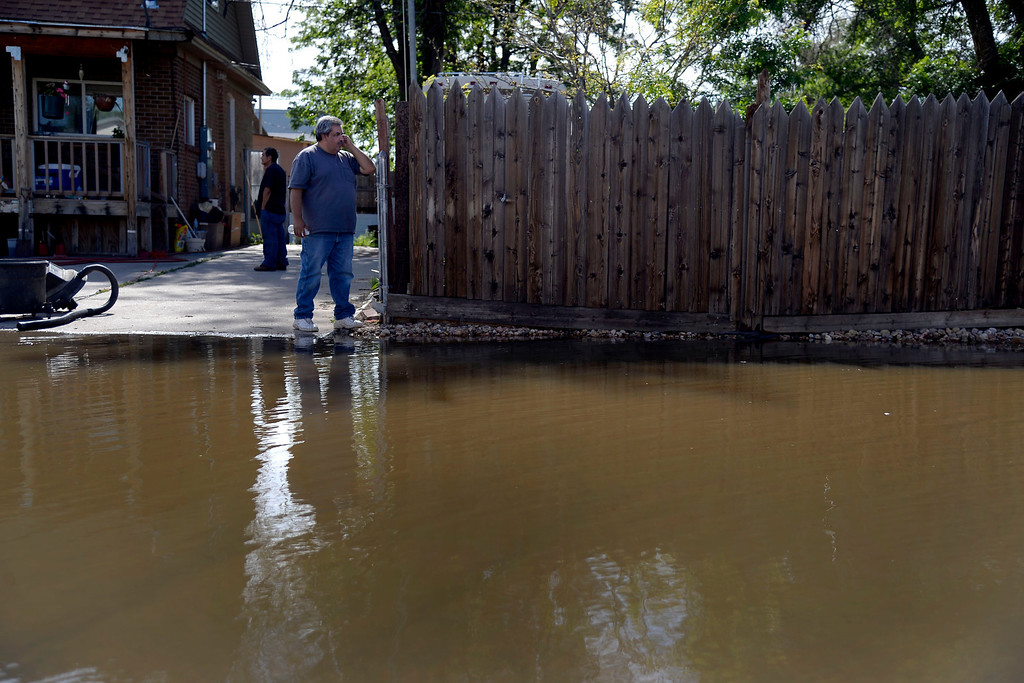 . Leo Pirto talks on the phone as he looks at the water after an area of town flooded. A heavy rain caused parts of Greeley to flood on Monday, June 2, 2014. (Photo by AAron Ontiveroz/The Denver Post)