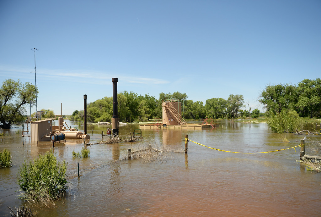 . Oil and gas equipment is surrounded in flood water near the Poudre River in northwest Greeley, June 2, 2014. A flood warning for the Poudre River near Greeley has been extended through Sunday. (Photo by RJ Sangosti/The Denver Post)