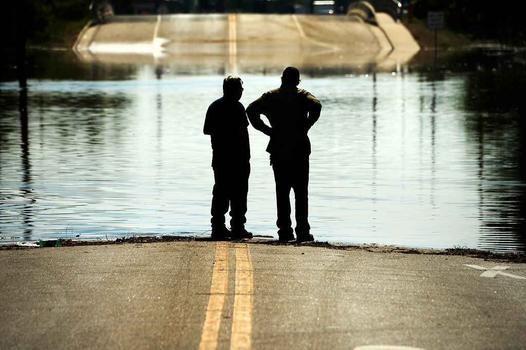 . Two men stand at the edge of the flood water as it continues to rise along the Poudre River in Greeley, June 3, 2014. A flood warning for the Poudre River near Greeley has been extended through Sunday. (Photo by RJ Sangosti/The Denver Post)