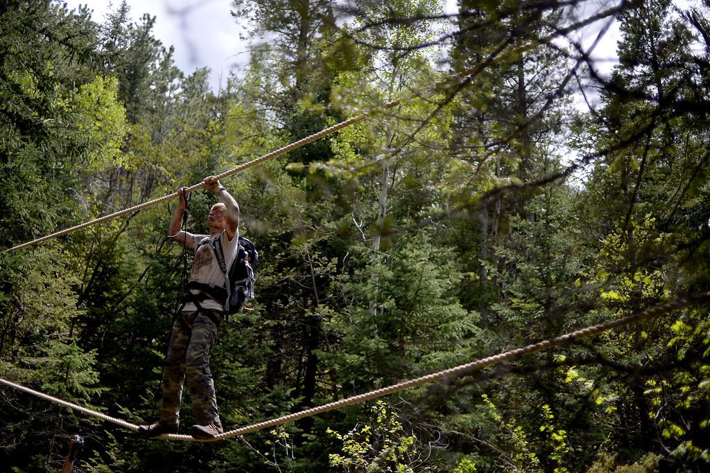 . WARD, CO - JUNE 10: Taylor Bond works his way across a rope bridge. Bear Grylls survival school at Glacier View Ranch near Ward, Colorado on Tuesday, June 10, 2014. (Photo by AAron Ontiveroz/The Denver Post)