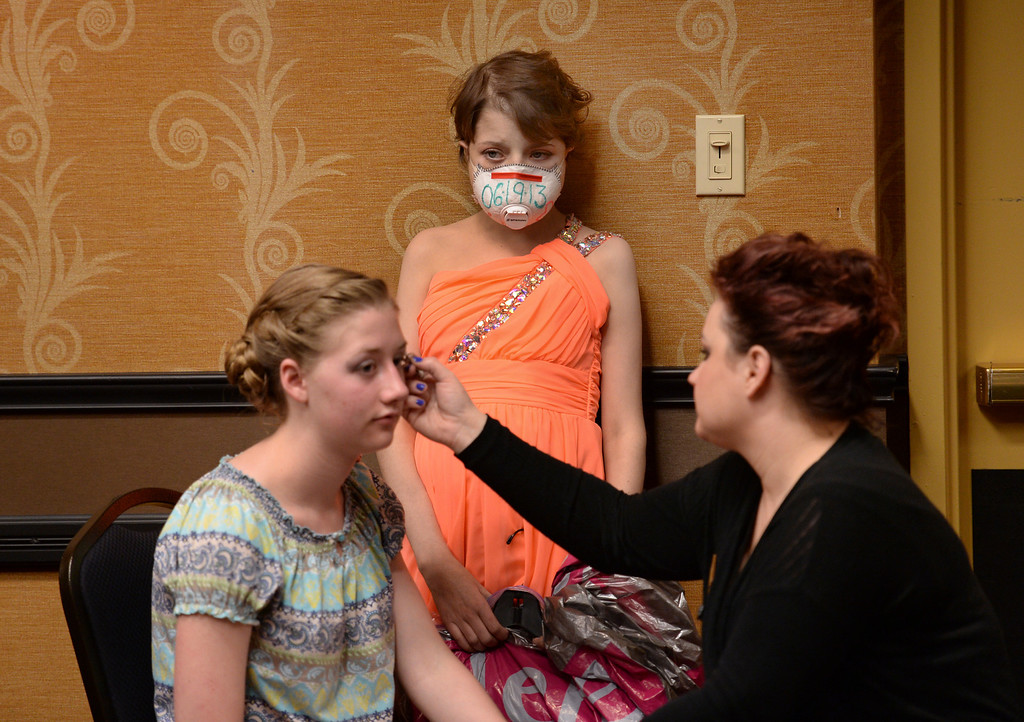 . DENVER, CO - JUNE 13: Ashleigh Orosz, center, waited for her twin sister Jessica to finish with her makeup before he Children\'s Hospital prom Friday night. Ashleigh will soon celebrate the one year anniversary of her bone marrow transplant, the date of which is printed on the face mask she wears.  Children\'s Hospital hosted a prom for teens that might have missed their regular prom due to medical issues. The event was held at the Double Tree Hotel Friday night, June 13, 2014. The prom provides patients to have the opportunity to experience one of the biggest rites of teen passage. (Photo by Karl Gehring/The Denver Post)