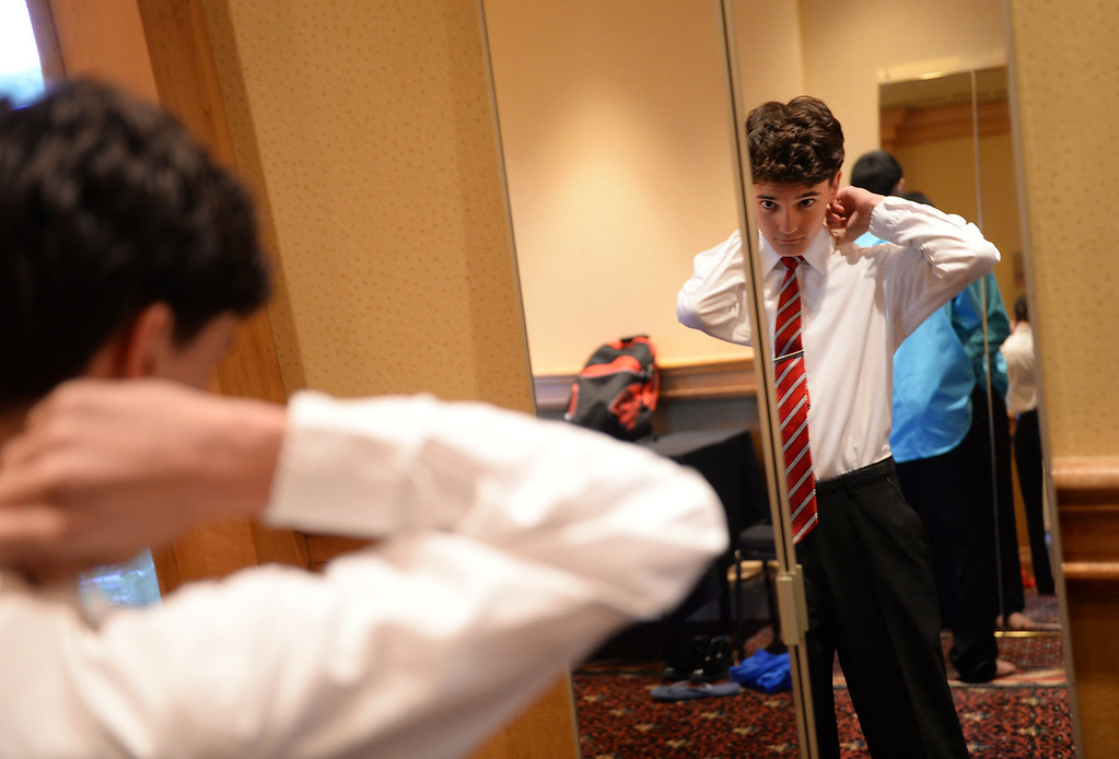 . DENVER, CO - JUNE 13: Zach Miller, age 15, tied his necktie in a mirror before the Children\'s Hospital prom Friday night. Miller has a mild form of cerebral palsy. Children\'s Hospital hosted a prom for teens that might have missed their regular prom due to medical issues. The event was held at the Double Tree Hotel Friday night, June 13, 2014. The prom provides patients to have the opportunity to experience one of the biggest rites of teen passage. (Photo by Karl Gehring/The Denver Post)