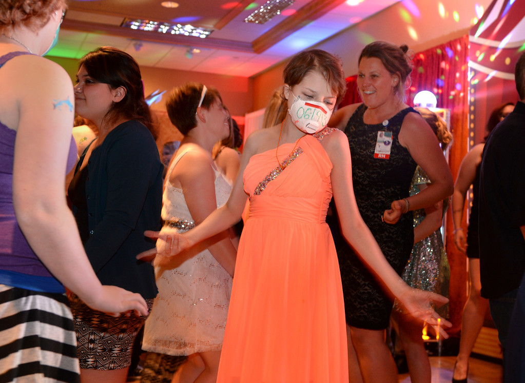 . DENVER, CO - JUNE 13: Ashleigh Orosz, age 15, partied with friends at the Children\'s Hospital Prom Friday night. Orosz wears a mask with the date of her bone marrow transplant (6-19-2013) from last year. Children\'s Hospital hosted a prom for teens that might have missed their regular prom due to medical issues. The event was held at the Double Tree Hotel Friday night, June 13, 2014. The prom provides patients to have the opportunity to experience one of the biggest rites of teen passage. (Photo by Karl Gehring/The Denver Post)