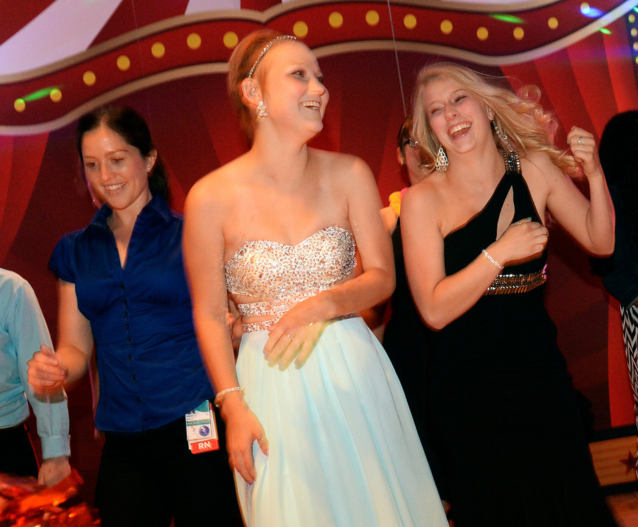 . DENVER, CO - JUNE 13: Olivia Current, center, hit the dance floor with her cousin Emily Pittsinger, right, at the Children\'s Hospital Prom Night. Current began the day with dialysis at the hospital, something she does three times per week after a bone marrow transplant three and a half years ago.  Children\'s Hospital hosted a prom for teens that might have missed their regular prom due to medical issues. The event was held at the Double Tree Hotel Friday night, June 13, 2014. The prom provides patients to have the opportunity to experience one of the biggest rites of teen passage. (Photo by Karl Gehring/The Denver Post)