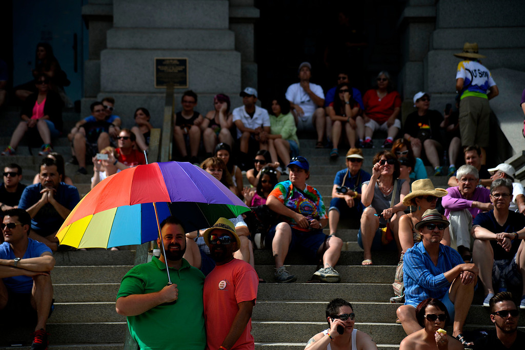 . DENVER, CO - JUNE 22: Bo Gascoigne and Reggie Smith stand beneath a pride umbrella on the north steps of the Colorado State Capitol Building during the PrideFest 2014 parade in downtown Denver. Thousands of people gathered in the city to enjoy a bevy of events including dancing, food and music on Sunday, June 22, 2014. (Photo by AAron Ontiveroz/The Denver Post)