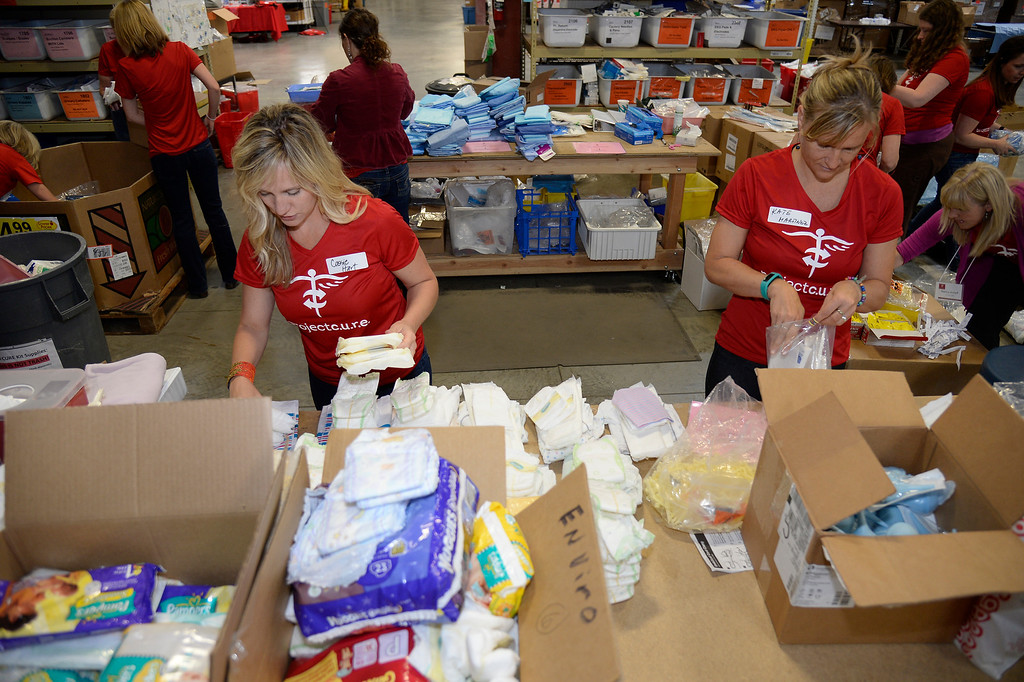 . Cassie Hart (L) and Kate  Martinez with Project C.U.R.E. put together Medical Supplies and Equipment in boxes to be shipped out.  (Photo by John Leyba/The Denver Post)