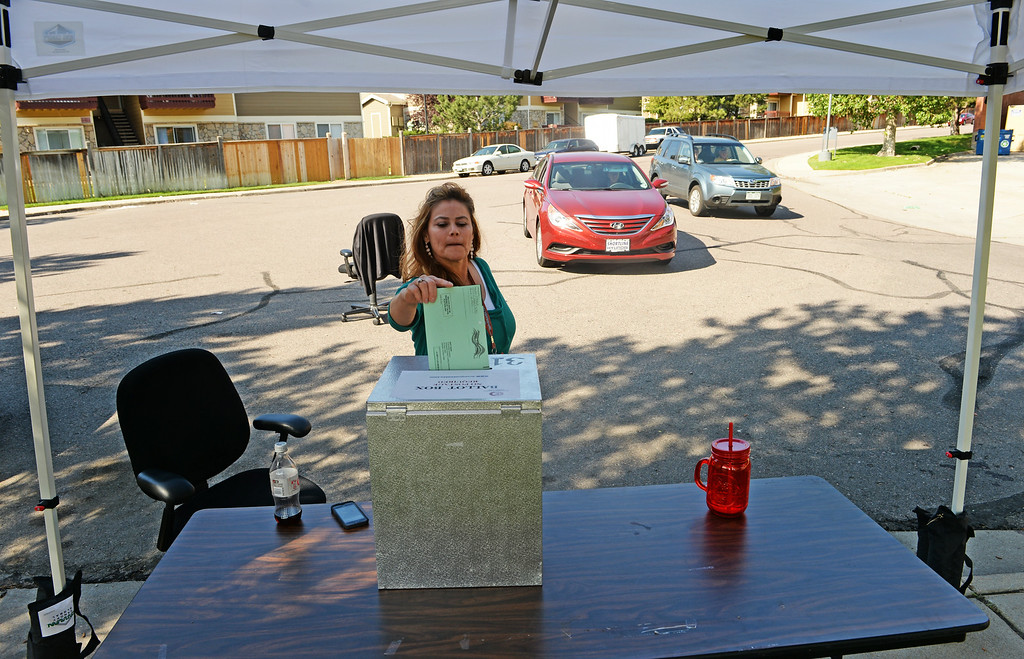. Tressie Landau, of Arapahoe County Clerk and Recorders Office, puts a ballot in the drop box outside Arapahoe County Clerk and Recorders offices in Aurora, June 24, 2014. Today is the final day of voting in the primaries in Colorado. (Photo by RJ Sangosti/The Denver Post)