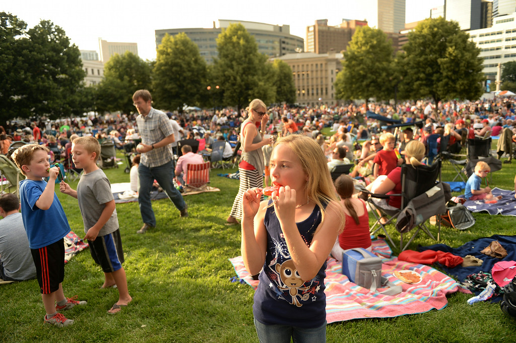 . DENVER, CO - JULY 3: Tatum Mendelsberg, age 10, enjoyed a popsicle as vening light cast a warm glow on thousands of people packing Civic Center Park waiting for the show to start. The Civic Center Conservancy put on an Independence Eve show complete with food, live music, and fireworks Thursday night, July 3, 2014. The University of Colorado a cappella group Mix shared the stage with Hazel Miller and the Denver Municipal Band. Photo by Karl Gehring/The Denver Post